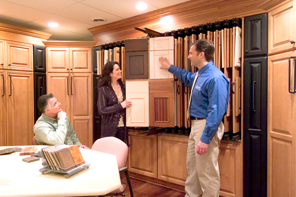 A franchisee shows cabinet design options to two clients in a showroom.