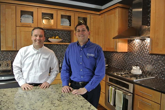 Two DreamMaker franchisees, one in a white, branded button-down and the other in a blue, branded button-down, stand in a remodeled kitchen.