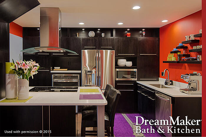 A contemporary-style kitchen, with orange walls, stainless steel appliances, black cabinetry and a purple rug. The DreamMaker® Bath & Kitchen logo is in the lower-right corner.