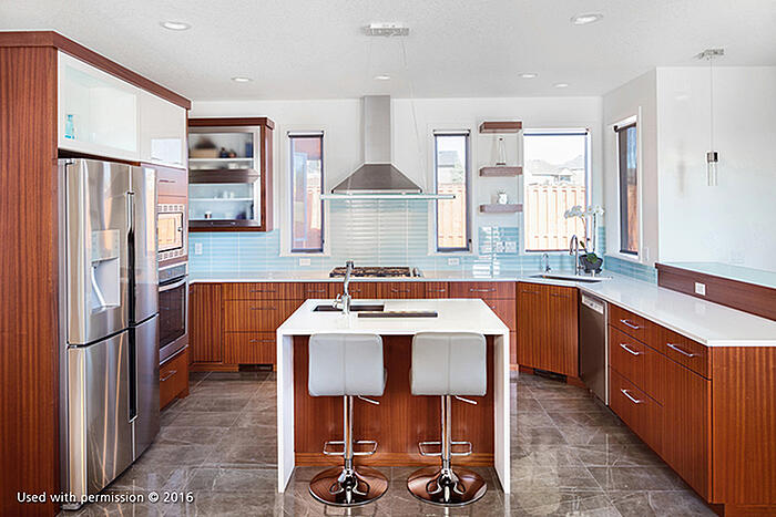 A contemporary kitchen remodel, with white countertops and stools, a marble-tiled floor, wooden cabinetry, stainless steel appliances and sky-blue tiling along the walls.