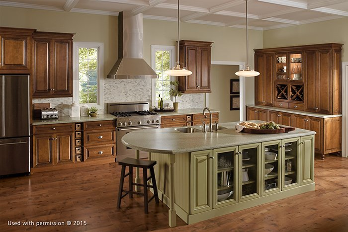 A wide view of a kitchen, with a light olive-green island counter, hardwood floor and wooden cabinetry.