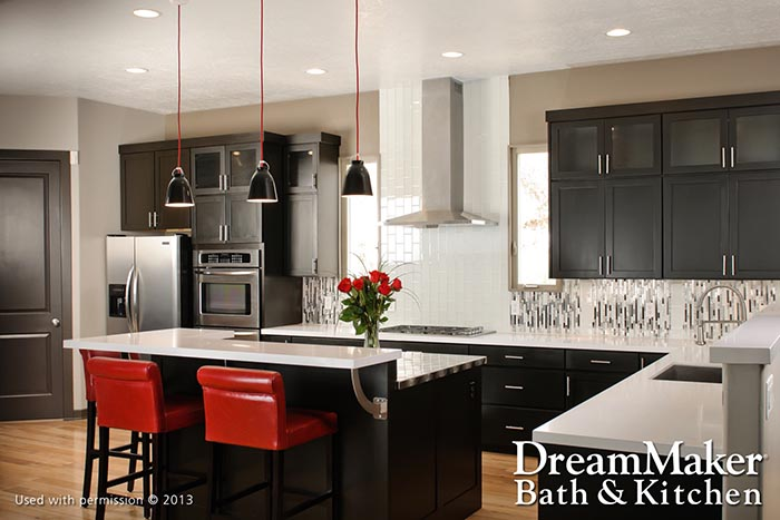 A modern, minimalist kitchen design with white counters, black cabinets and red seating.