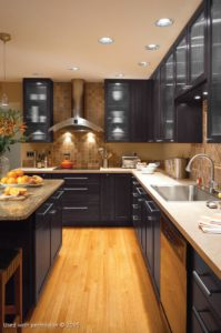 A modern kitchen remodel, with black cabinets, light-brown hardwood floors and stainless steel fixtures and appliances.