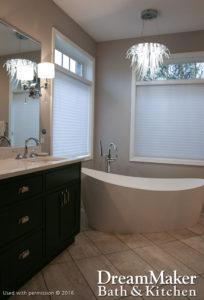 A modern bathroom with a chandelier over a white bathtub, marble sink and black cabinet.