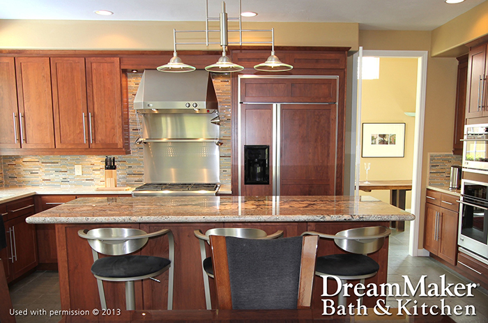 A modern kitchen, with a marble island, wood-surfaced cabinets and refrigerator, stainless steel stove and black-cushioned stools.