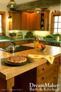 A kitchen remodel with brown wooden cabinets, flowers on the countertops, a bowl of apples and oranges and a freshly made pastry cooling on the kitchen island.