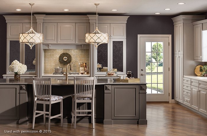 A white, blue and gray kitchen remodel features flowers and coffee sitting on the kitchen island, and two hanging white lights illuminating the room.
