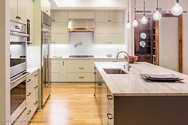 A brightly lit kitchen remodel, with light hardwood flooring, bare bulb lights, off-white cabinets, a white tile backsplash and a marbled counter on the kitchen island.
