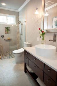 A bathroom with white tile walls and floors, a white counter with a raised sink, and brown cabinets.