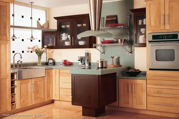 A modern kitchen remodel, with light wooden cabinet fronts and flooring, a dark-brown stovetop and faded teal countertops.