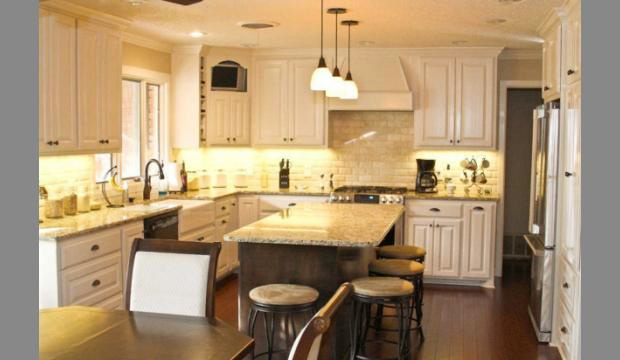 A beautiful kitchen with granite countertops, a large island and pendant lighting