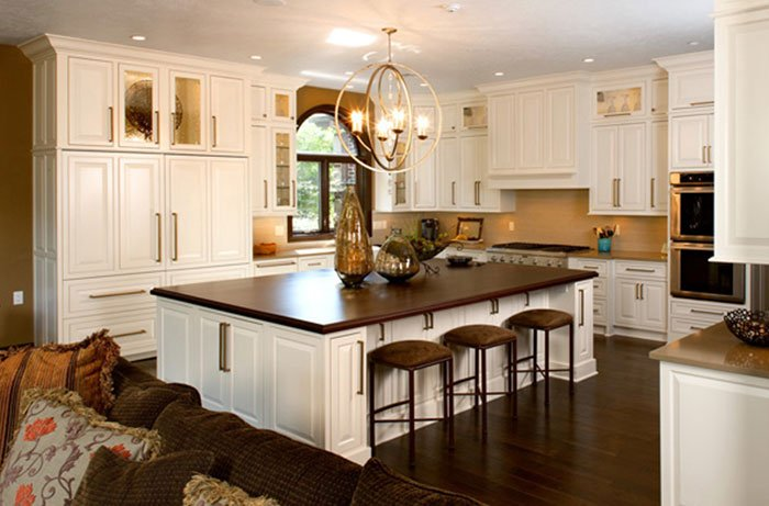 A kitchen with white cabinets including an island with a brown wooden table top. An chandelier hangs above the kitchen island, and a living room couch is partially visible in the foreground.