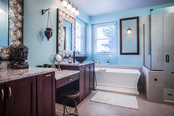 A bathroom remodel with sky-blue walls, brown cabinets with marble countertops and a separate bathtub and shower.