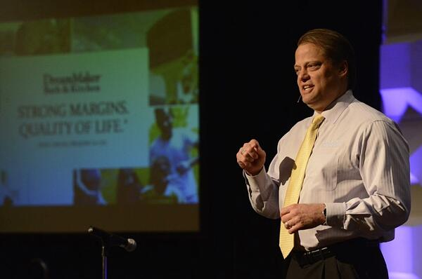 """DreamMaker President and CSO Doug Dwyer speaks on a stage; a screen with the DreamMaker logo and """"Strong Margins. Quality of Life."""" is slightly out-of-focus in the background."""