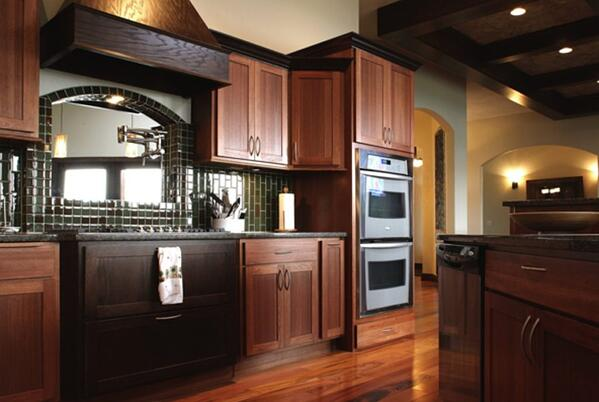 A kitchen design with dark wood cabinets and hardwood floors, with a forest green tile backsplash along the wall.