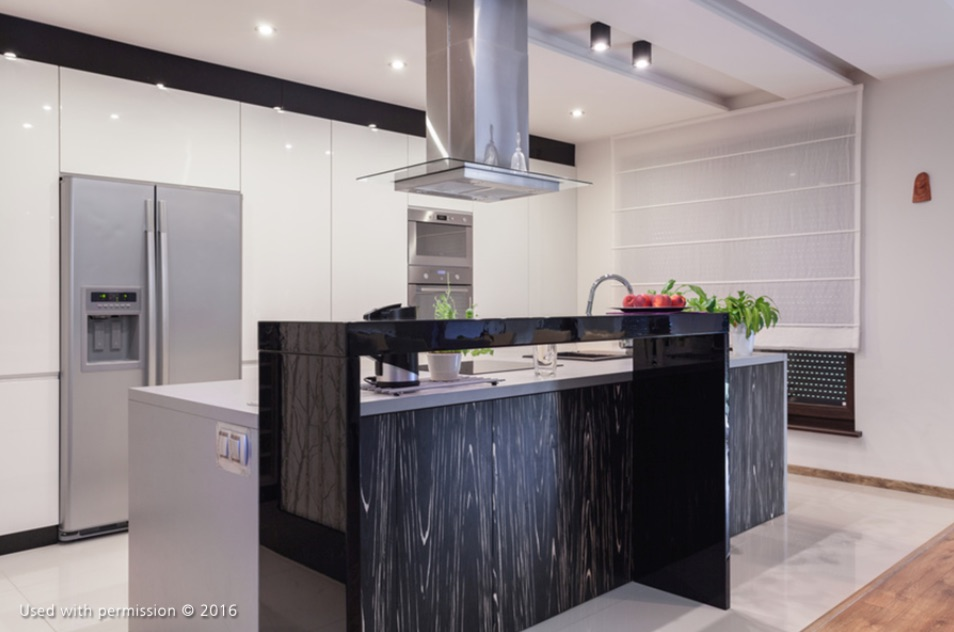 A modern kitchen remodel, with white walls, stainless steel appliances and a vent over a black marble kitchen island.