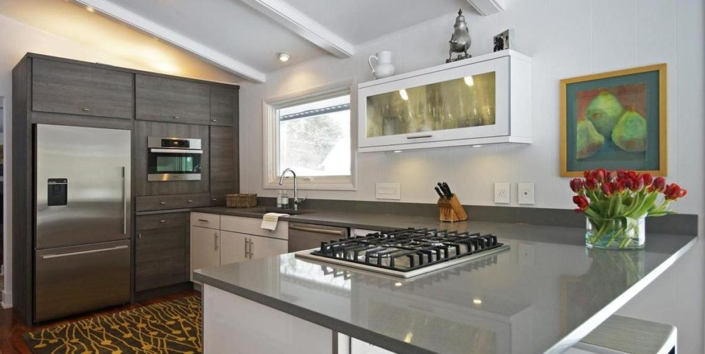 A kitchen remodel showcasing sleek gray countertops, stainless steel appliances and a mix of white and gray wooden cabinets. A painting of pears and a vase full of red flowers are visible at the right side of the frame.