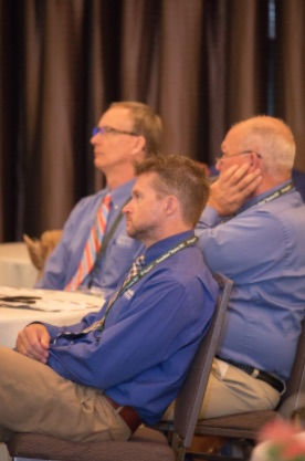 Three franchisees sitting at a banquet table concentrate on a speaker who's out of frame.