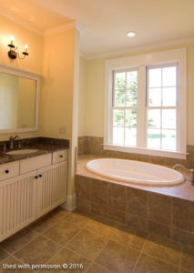 A bathroom with light brown tiles on the floor and tubs, off-white walls, a black marble countertop and a large window.