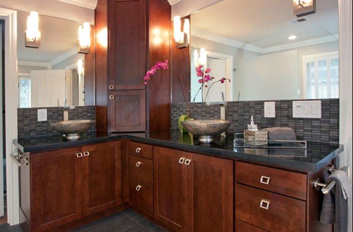 A modern bathroom design with large mirrors, a black countertop that wraps around the corner and dark wooden cabinets.