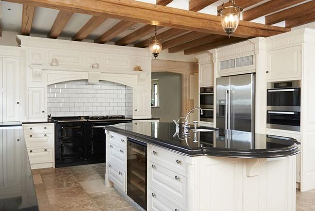 A kitchen remodel with beige floor tiles, white cabinets and black countertops and appliances.