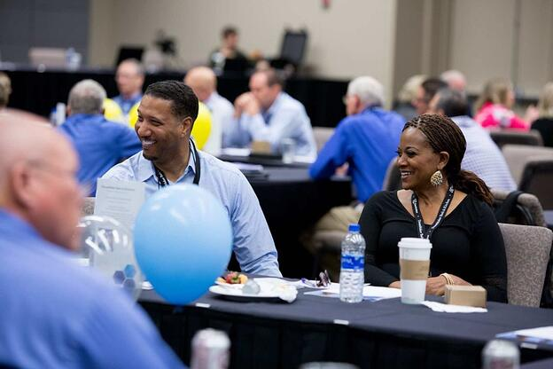 Two smiling franchisees sit at a table in a large conference room. Other attendees are visible in the foreground and background.