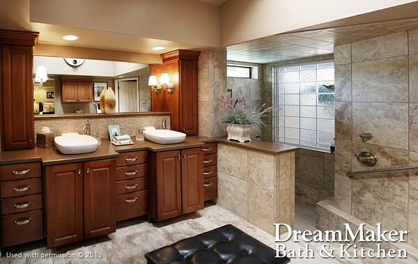 A bathroom with textured beige tile, two raised sink basins, dark wooden cabinets and light pink flowers with silvery foliage in a rectangular vase next to the shower.