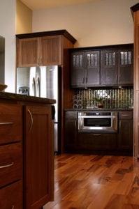 A kitchen remodel with dark wooden cabinets, an olive-green tile backsplash and a hardwood floor.