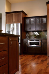 A kitchen remodel with dark wooden cabinets, an olive-green tile backsplash and a hardwood floor.