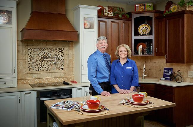DreamMaker franchise owners Glen and Denise Borkowski pose for a photo in a model kitchen in their Design Center.