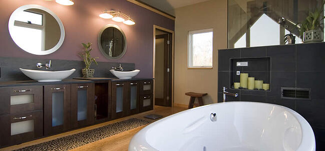 A bathroom remodeling project, featuring black cabinets with two sinks, a standalone porcelain tub, and circular mirrors on a purple wall above the sinks.