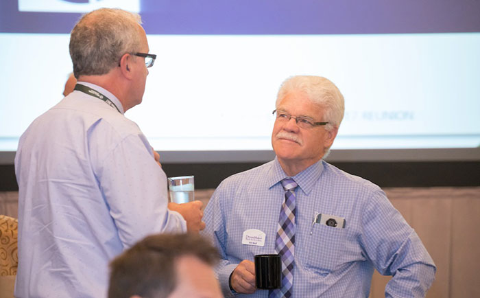 Two franchisees hold a conversation in front of a projector screen.