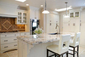 A kitchen with white cabinets and seats, a marble countertop and brown tile wall, with a glass bowl of fruit sitting on the counter.