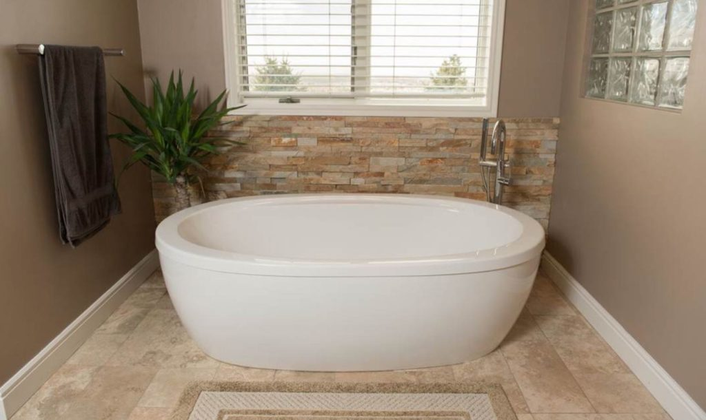 A white ceramic bathtub on beige floor tiles with light brown paint and small, patterned tiles on the back wall beneath a window. A towel and green plant can be seen to the left of the tub.