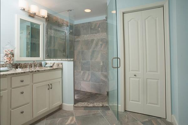 A view of a bathroom remodel with gray tiles on the floor and walk-in shower, off-white doors and cabinets and light blue walls.