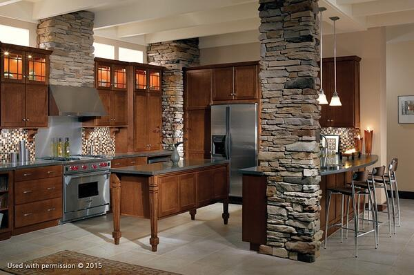 A kitchen remodel with stone columns, hardwood cabinets, an off-white tile floor and dark gray countertops.