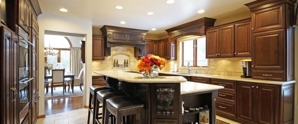 A view of a newly remodeled kitchen, with dark wooden cabinets, a marble backsplash and counters, leather-upholstered stools and a centerpiece of flowers on the kitchen island.