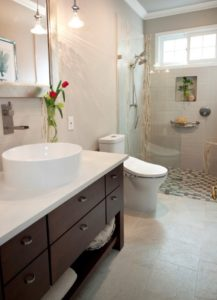 An image of a bathroom remodel with white floors, dark wooden cabinets and a pair of flowers next to the sink.