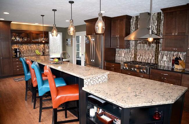 An image of a kitchen remodel with orange and blue chairs, a marbled kitchen island, dark wooden cabinets and a black, gray and white tile backsplash.