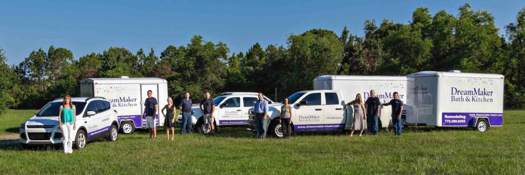 The team from the Southeast Florida DreamMaker poses in a grassy field with several DreamMaker-branded vehicles and equipment trailers.