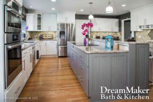 A remodeled kitchen showcases a granite-topped island with gray beadboard and cabinets; sleek white cabinets with stainless appliances; beige tile backsplashes; and hardwood floors.