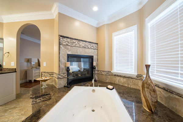 A fully remodeled bathroom featuring a fireplace next to the bathtub.
