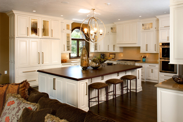 A fully remodeled kitchen showcasing cabinets, the kitchen island and a chandelier.