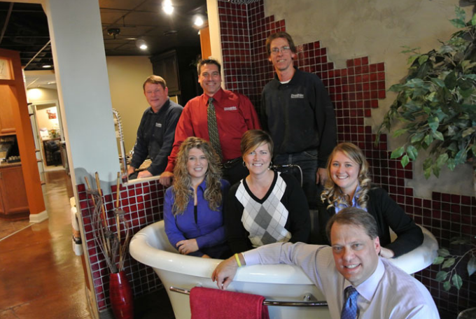 Mike Fischer, in the red shirt, and DreamMaker Bath & Kitchen President Doug Dwyer, foreground, pose with Mike's staff at the Design Center in Lansing, Michigan.