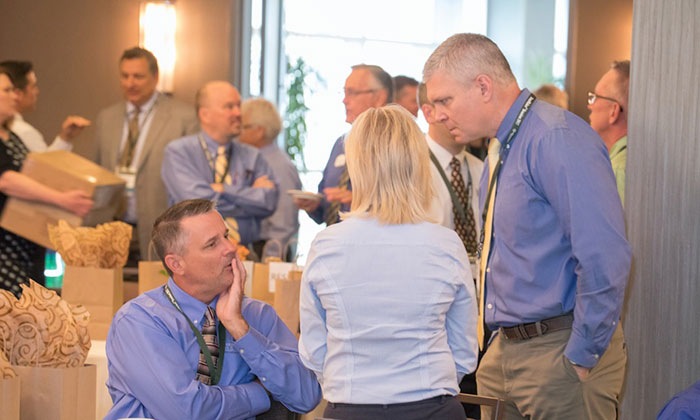 Two male franchisees and one female franchisee discuss something in the banquet hall as other attendees can be seen milling about in the background.