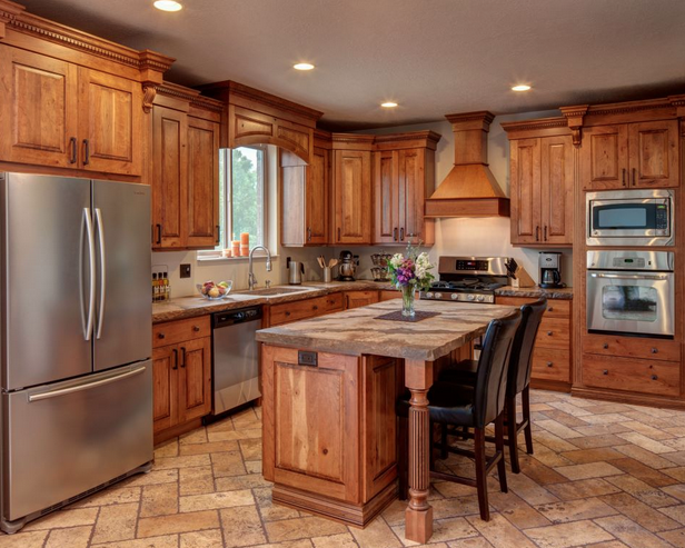 Picture of a kitchen with wooden cabinets and brown stone counters and floors, stainless steel appliances, and tan walls.