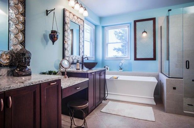 A modern bathroom features pale blue walls, beige diamond tile, a garden tub next to a glass-walled shower, and a dark cabinetry, granite-topped double sink with vanity.