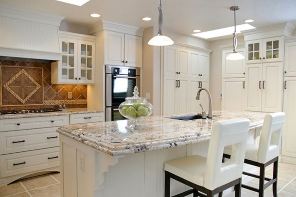 A modern kitchen features white cabinetry, a pale granite-topped center island with two white chairs, and beige large-tile floors. A decorative jar of green apples sits on the island, which also has a sink.