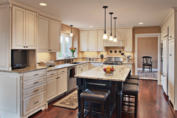 An image of a recent kitchen remodel, with white cabinets around the wall and pendant lights hanging over the dark-wood, marble-topped center island.