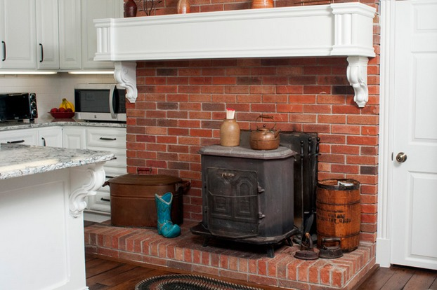 The hearth is now a focal point in the room since it contrasts with the bright countertops and cabinetry.